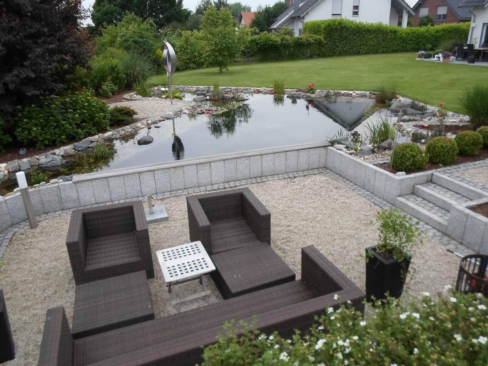 Schwimmteichanlage mit tieferliegender Terrasse mit Palisadeneinfassung