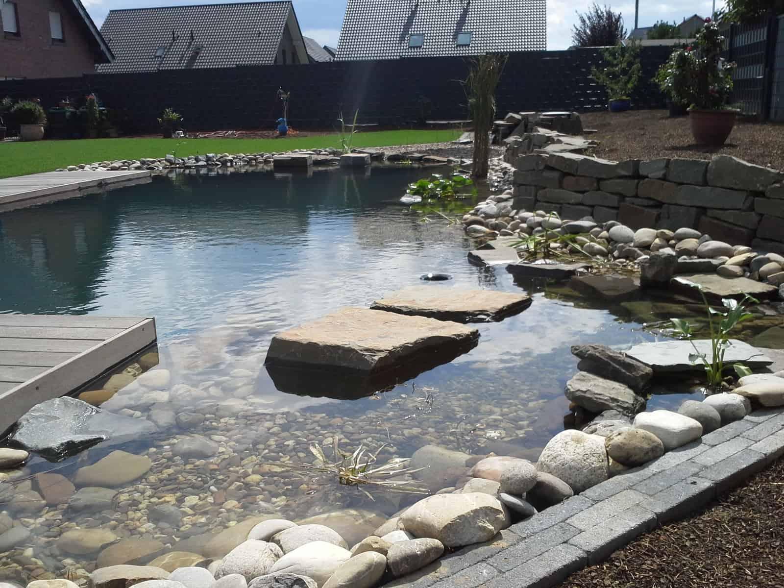 Schwimmteichanlage mit Holzterrasse und Natursteinmauer